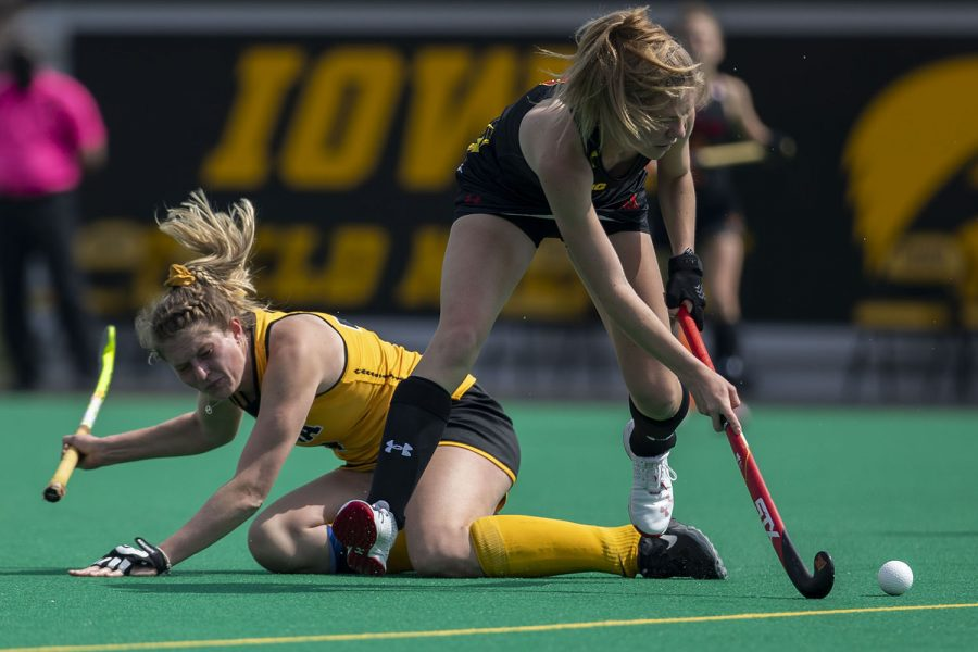 Iowa midfielder Ellie Holley falls while trying to steal the ball during the second quarter of a field hockey game against Maryland on Sunday, April 4, 2021 at Grant Field. The Hawkeyes defeated the Terrapins, 3-0.