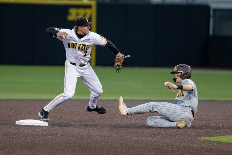 Iowa shortstop Brendan Sher throws to first after tagging second for a double play during a baseball game between Iowa and Minnesota at Duane Banks Field on April 9, 2021. The Hawkeyes defeated the Gophers 7-0.