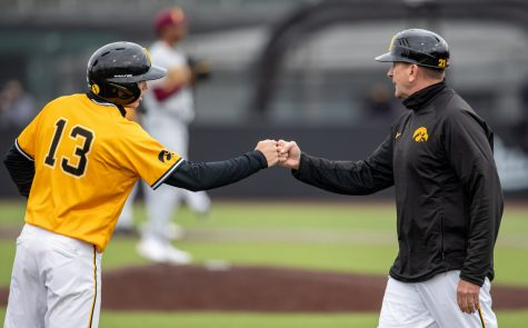 Iowa second basemen Michael Sergers fist bumps head coach Rick Heller during a baseball game between Iowa and Minnesota at Duane Banks Field on Sunday, April 11, 2021. The Hawkeyes defeated the Gophers 18-0.