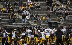 Fans watch as the Hawkeyes huddle after Iowa football spring practice on Saturday, April 17, 2021 in Kinnick Stadium.