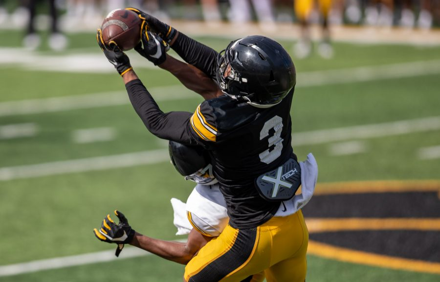 Iowa wide receiver Tyrone Tracy Jr. catches a ball over a defender during Iowa football spring practice at Kinnick Stadium on Saturday, April 17, 2021.