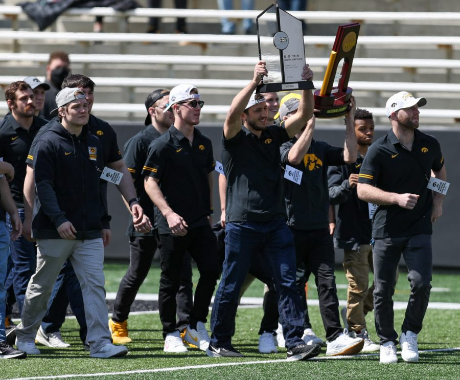 The Iowa wrestling team lifts up their trophies during Iowa football spring practice at Kinnick Stadium on Saturday, April 17, 2021.