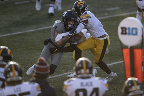 Saturday Dec. 5, 2020; Champaign, Illinois, USA; Illinois wide receiver Casey Washington (left) is tackled by Iowa defensive back Matt Hankins (right) during the second quarter of the Iowa v. Illinois football game at Memorial Stadium.