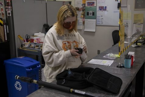Senior and journalism major, Eden Smith, cleans equipment after a student returns it in Equipment Checkout located in the Becker Communication Studies Building at the University of Iowa on Wednesday, March 31, 2021. (Grace Smith/The Daily Iowan)