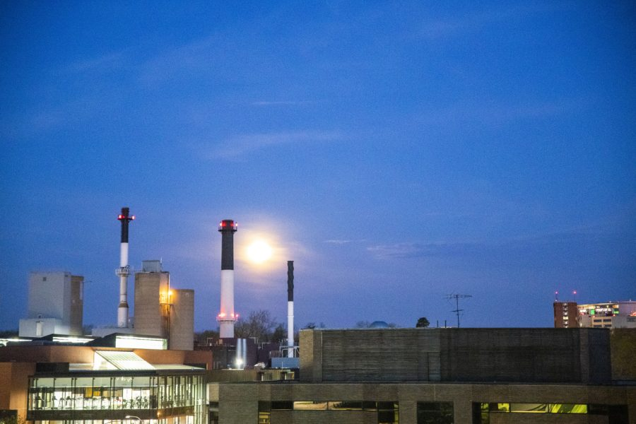 The full moon begins to set behind the power plant  on Monday April 26, 2021.