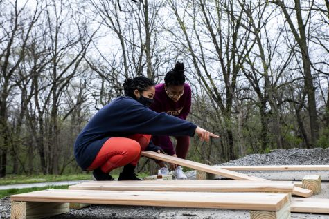 Aluna-Aro Olaniyi (left) and Cherish Cornett (right) discuss how to lay out the boards for the design of the boxes on Sunday, April 11, 2021. The boxes will be used to grow vegetables in a community garden located behind the Afro-House.