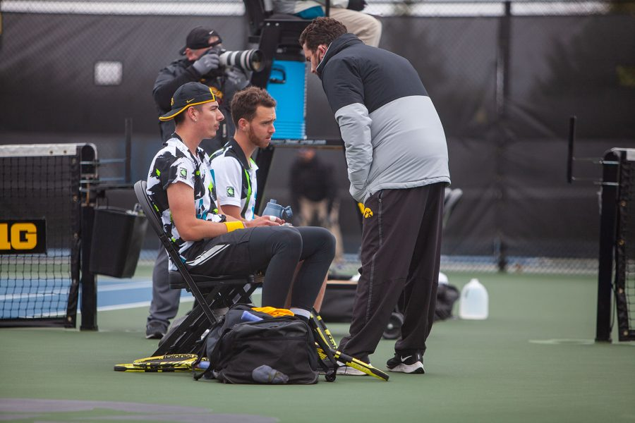 Iowa's Nikita Snezhko (left) and Kareem Allaf (middle) listen to head coach Ross Wilson (right) during a men's tennis meet between Iowa and Northwestern on Sunday, April 11 at the Hawkeye Tennis and Recreation Complex. The Wildcats defeated the Hawkeyes 6-1.
