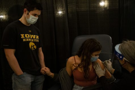 Fourth-year students, Grace Cannell and Ethan Fobbe, hold hands while Cannell receives her Pfizer COVID-19 vaccine at the Iowa Memorial Union at the University of Iowa on Wednesday, April 21, 2021.