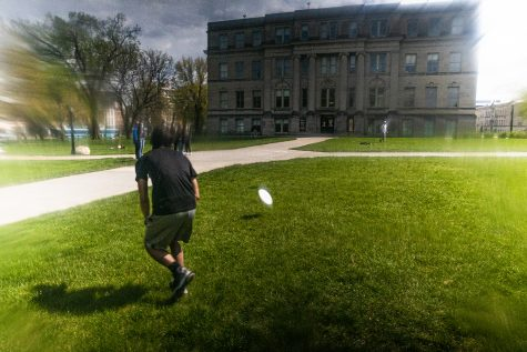 University of Iowa sophomore Kurt Bennett plays frisbee with a friend on the on the Pentacrest in downtown Iowa City on Thursday, April 29, 2021. Now that the weather has finally warmed up, Kurt and his friend decided to take a break from studying for finals and enjoy some time outside.