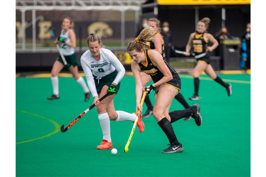 Iowa Midfielder Ellie Holley works past a defender during a field hockey game between Iowa and Michigan State at Grant Field on Friday, March 26, 2021. The Hawkeyes defeated the Spartans 5-0.
