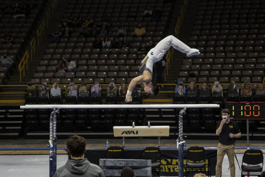 Iowa all-around Bennet Huang competes on the parallel bars during the Iowa v. Nebraska men's gymnastics meet in Carver-Hawkeye Arena on Saturday, March 20, 2021. Iowa defeated Nebraska with a score of 406.700 - 406.650. Huang placed third on the parallel bars with a score of 13.750.