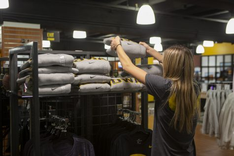 An Iowa Hawk Shop student employee places a sweatshirt on a display on Thursday, Oct. 31, 2019.