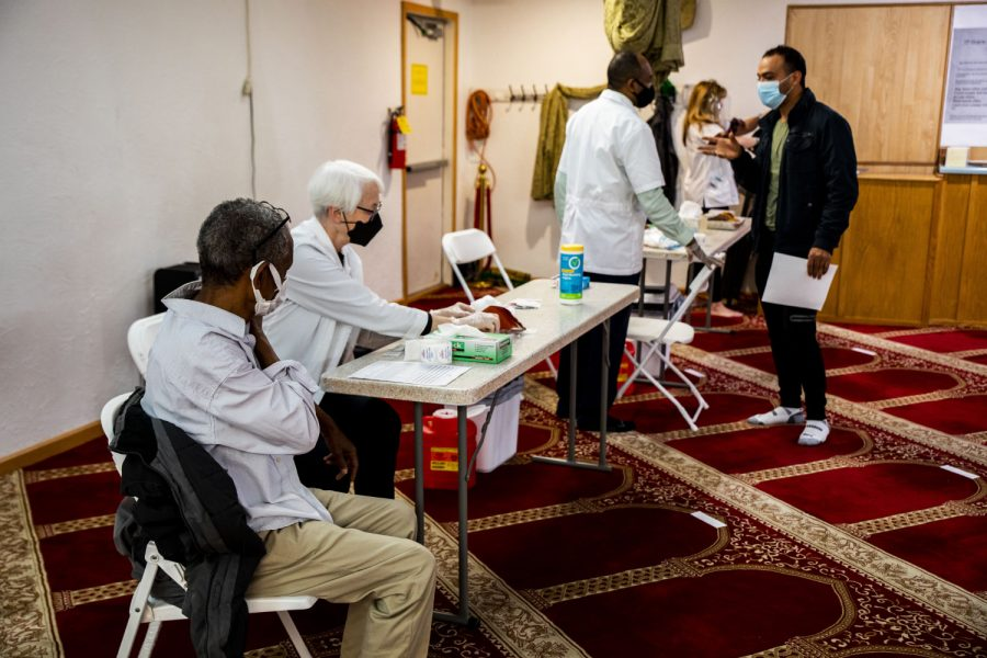 People wait for their vaccinations in the prayer room on Saturday, April 12, 2021. A clinic was being held by Hartig Pharmacy at the Al-Iman Mosque in Iowa City.