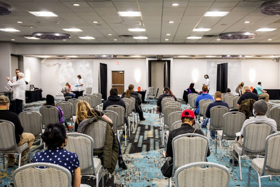 Customers wait to receive their first vaccine shot on Wednesday, April 14, 2021. Hartig Pharmacies held a clinic for hospitality workers at the Raddisson Hotel Conference Center in Coralville.