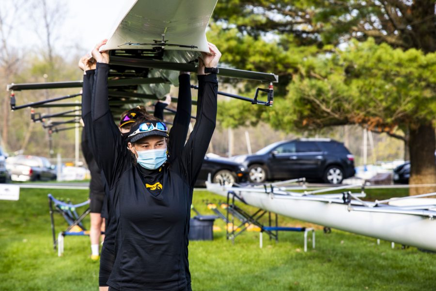 Iowa rowing moves their boat to the dock on Saturday, April 24, 2021 during The Iowa Rowing Regatta at Lake MacBride. Iowa competed against Minnesota, Wisconsin, Drake, and Kansas during the one-day event.