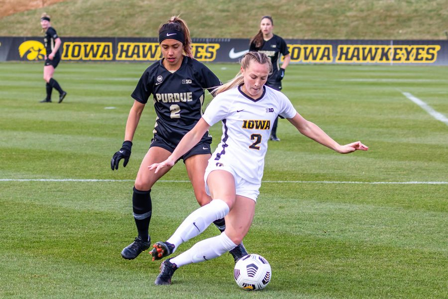 Iowa Midfielder Hailey Rydberg moves the ball away from Purdue Defender Julia Ware during the Iowa Soccer senior day game against Purdue on Mar. 28, 2021 at the Iowa Soccer Complex. Iowa defeated Purdue 1-0.