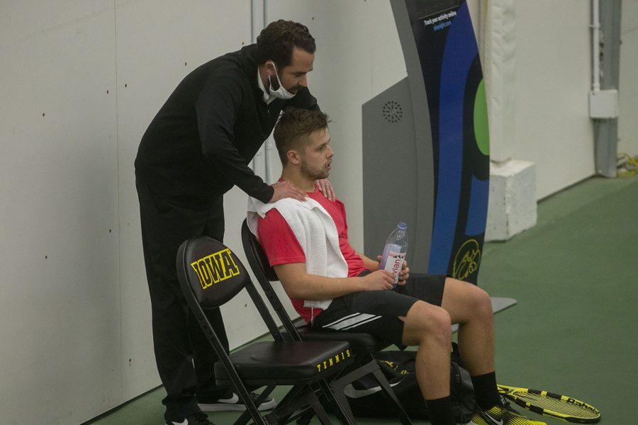 Iowa's coach, Ross Wilson, talks to player, Will Davies, as he sits in between sets during the Iowa Men's tennis meet v. Wisconsin in the Hawkeye Tennis and Recreation Complex on Friday, March. 12, 2021. The Hawkeyes defeated the Badgers 5-2.