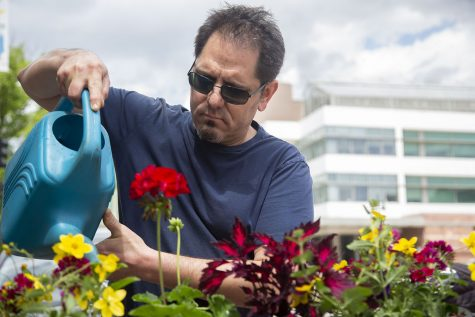 Nodo Downtown employee, Josh Silver, waters newly planted flowers outside of Nodo Downtown in Iowa City on Thursday, May 6, 2021.