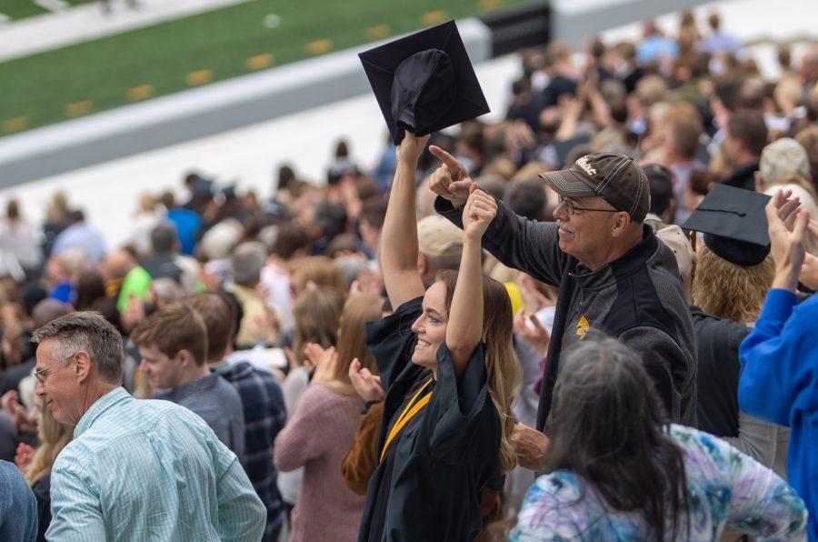 A graduate raises her cap to celebrate during the University of Iowa's celebration of graduates Sunday, May 16, 2021, at Kinnick Stadium. (Jerod Ringwald/The Daily Iowan)