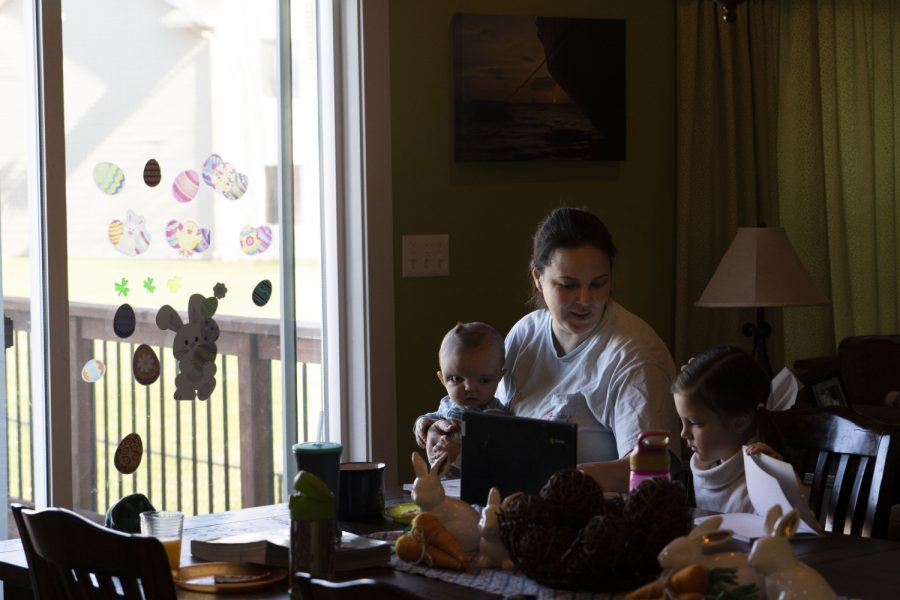 """Laura Greenwood sits at her kitchen table with her daughter Bridget, seven, and son Reid, one, on Thursday, April 1, 2021. """"The beginning of the pandemic was scary, very scary."""" Greenwood said. """"We were expecting a baby and there was a lot of uncertainty."""""""