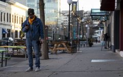 An individual waits outside before an away football game on Friday, Nov. 13, 2020 in Downtown Iowa City.