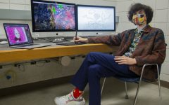 """Cinema and journalism major Jacob Smithburg poses for a portrait with his animations on screens behind him in an editing lab located at the Becker Communication Studies Building on Monday, April 26, 2021. Smithburg is an animator who spends hours working projects that he is interested in. """"Go with the flow, do the work, follow your gut,"""" Smithburg says. """"Be adventurous. Experiment and push the boundaries of a given medium! Go buckwild! Own it! Weirdness is the brand, baby! Also get a fun pair of socks. It's thrilling. It's fun. You'll love it. Go bananas."""""""