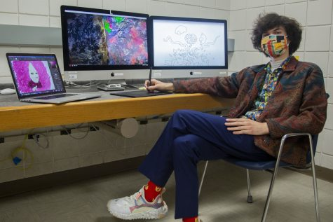 """Cinema and journalism major Jacob Smithburg poses for a portrait with his animations on screens behind him in an editing lab located at the Becker Communication Studies Building on Monday, April 26, 2021. Smithburg is an animator who spends hours working projects that he is interested in. """"Go with the flow, do the work, follow your gut,"""" Smithburg says. """"Be adventurous. Experiment and push the boundaries of a given medium! Go buckwild! Own it! Weirdness is the brand, baby! Also get a fun pair of socks. It"""