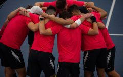 The Iowa's mens tennis team huddles during their meet v. Nebraska at the Hawkeye Tennis and Recreation Complex on Sunday, Feb. 28. The Hawkeyes defeated the Huskers with a score of 5-2. The team wears red, instead of the team colors, to protest the University of Iowa's decision to cut their program, making it their final season.