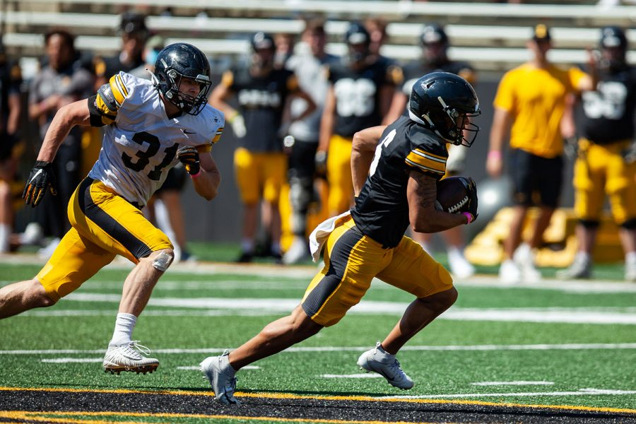 Iowa linebacker Jack Campbell (left) chases after Iowa wide receiver Keagan Johnson (right) during a spring practice at Kinnick Stadium on Saturday, May 1, 2021.