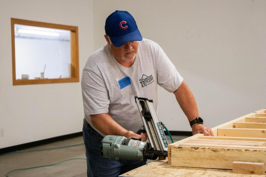 Steve Schornhorst, the construction manager on the Shelter House's board, helps build some walls for The 501 Project at a volunteer build before the ceremony on Thursday.