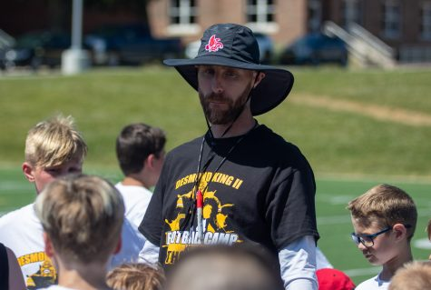 Iowa City High football coach Mitch Moore talks in a huddle during the Desmond King Football Camp at Iowa City High on Saturday, June 19, 2021. City High announced Moore as the new coach of the Little Hawks in November of 2020.