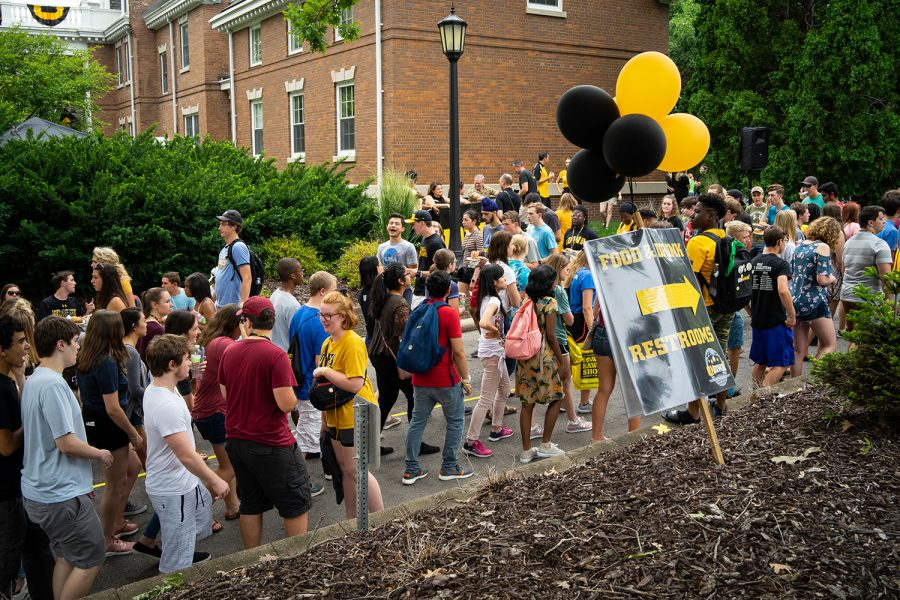 University of Iowa freshman line up for food and drinks outside the President's Mansion during the OnIowa President's Block Party on Sunday, August 19, 2018. OnIowa events help incoming university students engage and settle into their new environment.