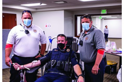 Asst. Fire Chief Nic Pruter left and Lt. William (Bill) Erb of the Coralville Fire Department stopped by to lend support to Sgt. Kyle Nicholson of the Coralville police Department on Thursday, July 22, 2021. At the time, Nicholson was donating blood during the Battle of the Badges Blood Drive.(Jeff Sigmund/Daily Iowan)