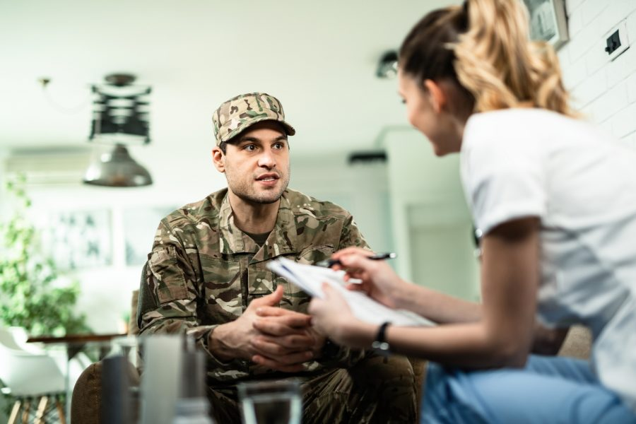 Young military man talking to healthcare worker who is visiting him at home.