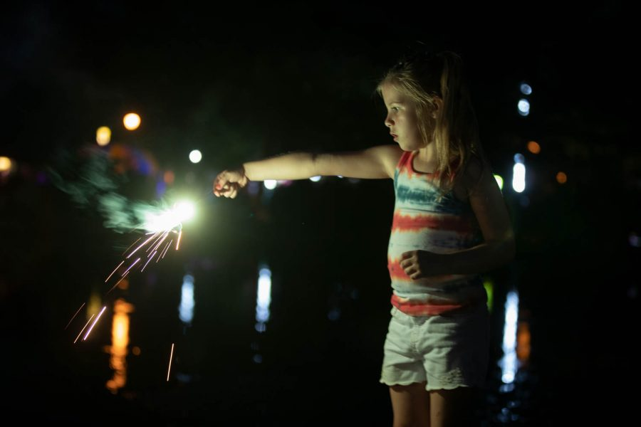 A little girl lights a sparkler at P.T. Morrison Park on July 4 2021.