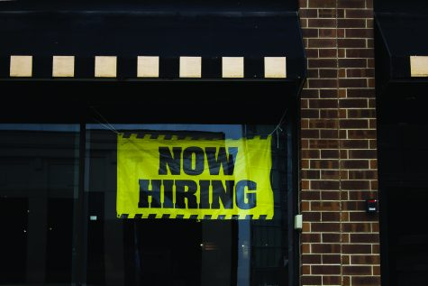 """A sign reads """"Now Hiring"""" in downtown Iowa City on Friday, July 23."""