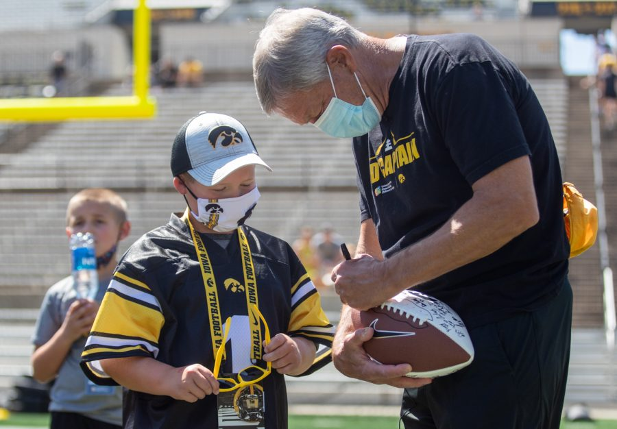 """Iowa head coach Kirk Ferentz signs a ball for kid captain Kale Schmidt during """"Kid's Day at Kinnick"""" inside Kinnick Stadium on Saturday, Aug. 14."""