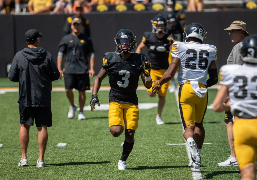 """Iowa wide receiver Tyrone Tracy Jr. high fives a teammate during """"Kid's Day at Kinnick"""" inside Kinnick Stadium on Saturday, Aug. 14."""