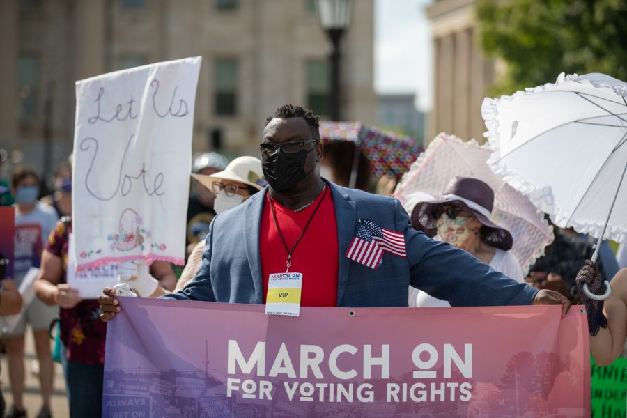 Iowa City Mayor Bruce Teague leads a march during a rally for voting rights at the Pentacrest on Saturday, Aug. 28.