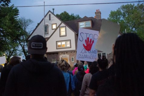 People stand in front of Phi Gamma Delta during a protest following sexual assault allegations against the University of Iowa's chapter of Phi Gamma Delta on Tuesday, Aug. 31, 2021.