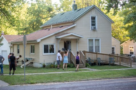Neighbors stand on a property after an FBI raid in Iowa City on Wednesday, Aug. 18. Damage can be seen on the side of the house after being hit by an armored truck during the raid.