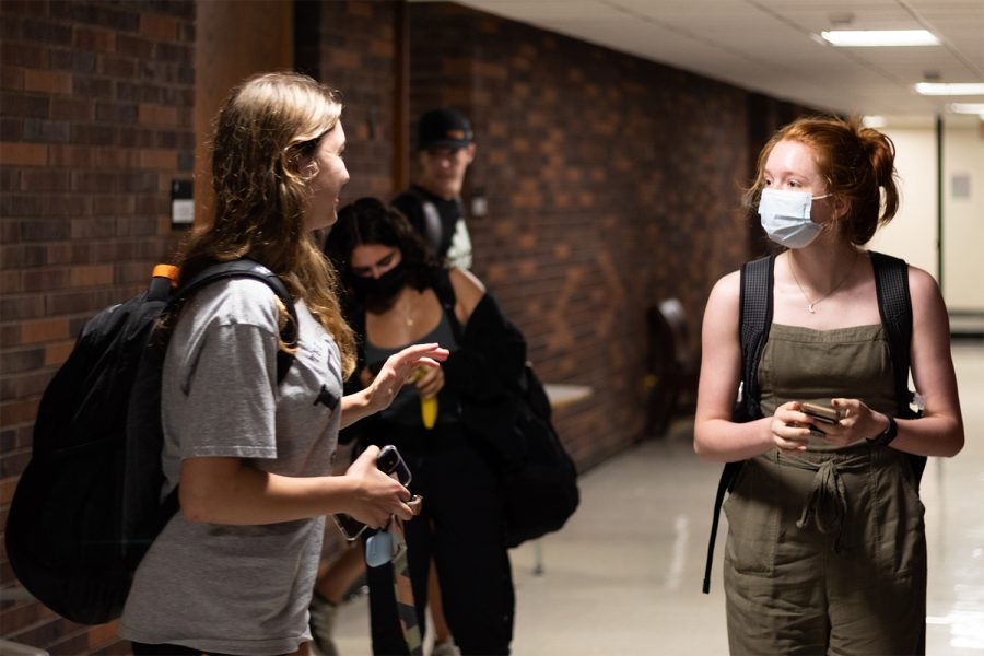 Two students are seen talking after class in the English Philosophy Building at the University of Iowa on Wednesday, Aug. 25, 2021. While masks are not required, some students still opt to wear masks on campus.