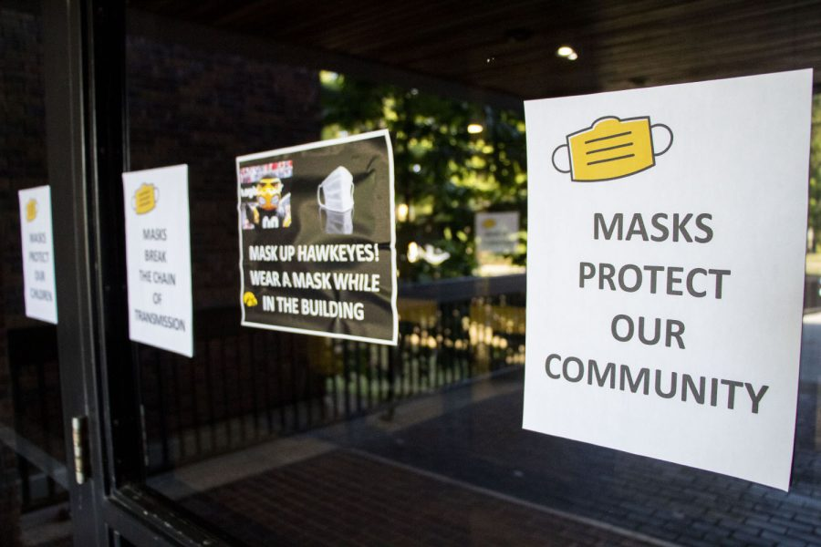 Signs encouraging students to wear masks in classrooms are seen on the doors of the English-Philosophy Building at the University of Iowa on Monday, Aug. 23, 2021.