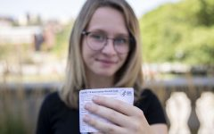First-year Jenna Sackett poses with her vaccination card on the Pentacrest at the University of Iowa on Tuesday, Aug. 24, 2021.