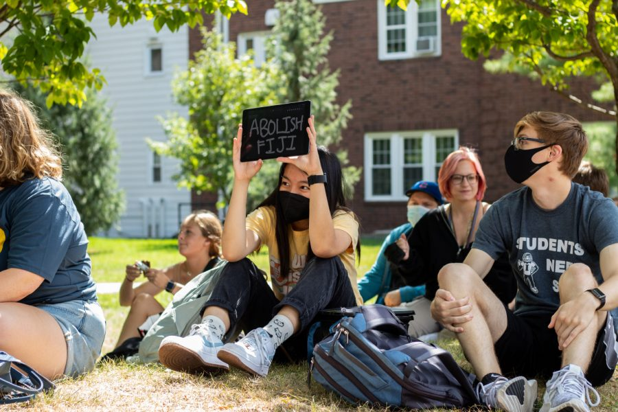 Protesters are seen sitting outside of the University of Iowa President's Residence following sexual assault allegations against the University of Iowa's chapter of Phi Gamma Delta on Wednesday, Sept. 1, 2021.