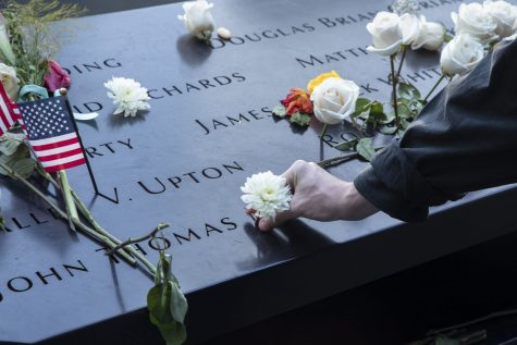 A citizen puts a flower in a victim's name at the 9/11 Memorial in New York City on Saturday, Sept.11, 2021, the 20th anniversary of the 9/11 attacks.