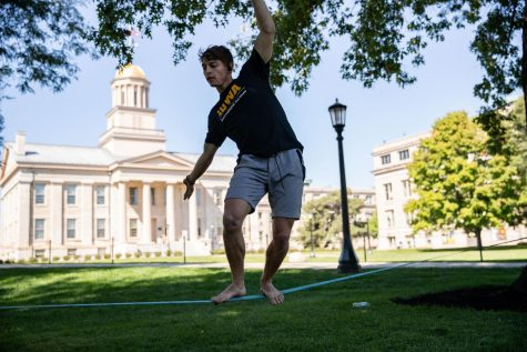 """University of Iowa graduate and personal trainer at the Campus Recreation and Wellness Center Ryan Renken trains his balance on a slackline on the Pentacrest on Thursday, Sept. 16, 2021. """"I want to try to start a slacklining club. I want all of these trees on the Pentacrest filled with slacklines,"""" Renken said."""