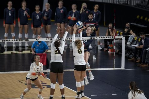 Illinois outside hitter Raina Terry spikes the ball as Iowa middle blocker Amiya Jones and setter Jenna Splitt attempt to block it during a volleyball game between Iowa and Illinois at Xtreme Arena in Coralville, Iowa, on Wednesday, Sept. 22, 2021. The Fighting Illini defeated the Hawkeyes with a score of 3-2.