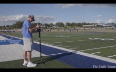 Student videographer Kayd Nissen films a high school football team.