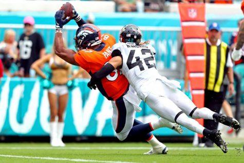 Sep 19, 2021; Jacksonville, Florida, USA; Denver Broncos tight end Noah Fant (87) scores a touchdown against Jacksonville Jaguars defensive tackle DaVon Hamilton (52) during the third quarter at TIAA Bank Field.